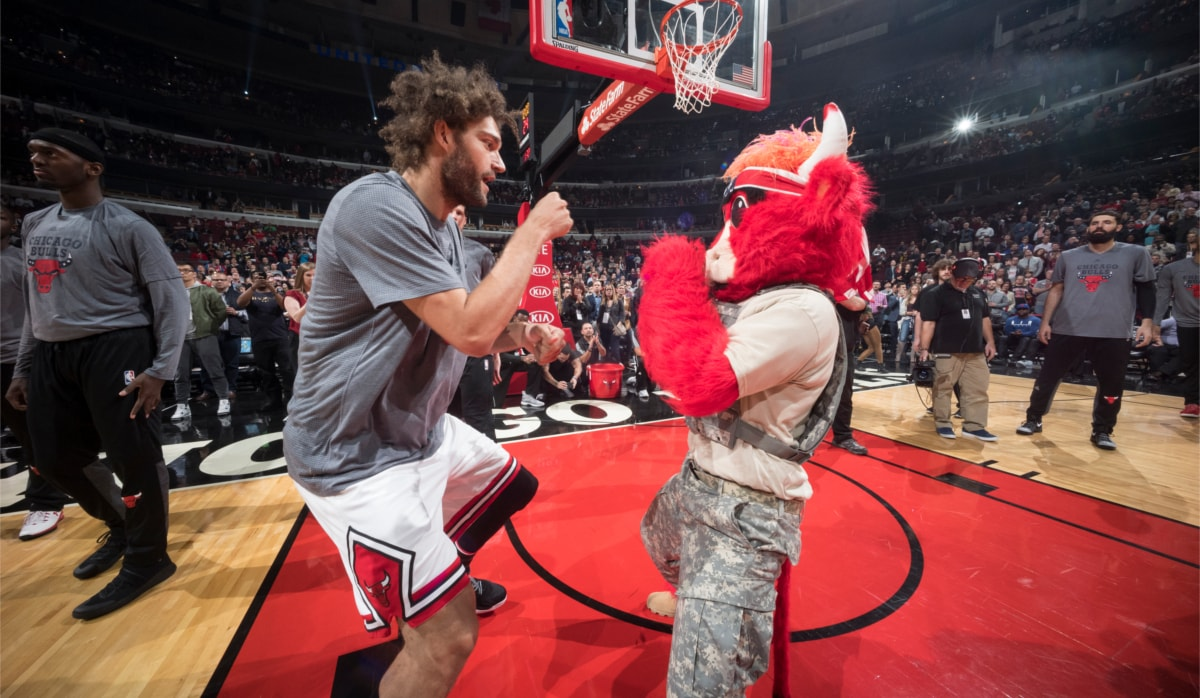 Robin Lopez of the Chicago Bulls with fists up in a boxing stance  squaring off with Benny the Bull.