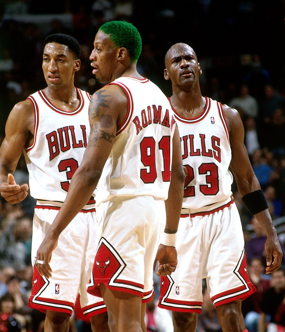 Scottie Pippen #33, Dennis Rodman #91, and Michael Jordan #23 of the Chicago Bulls catch their breath during a 1996 NBA game at the United Center in Chicago, Illinois.