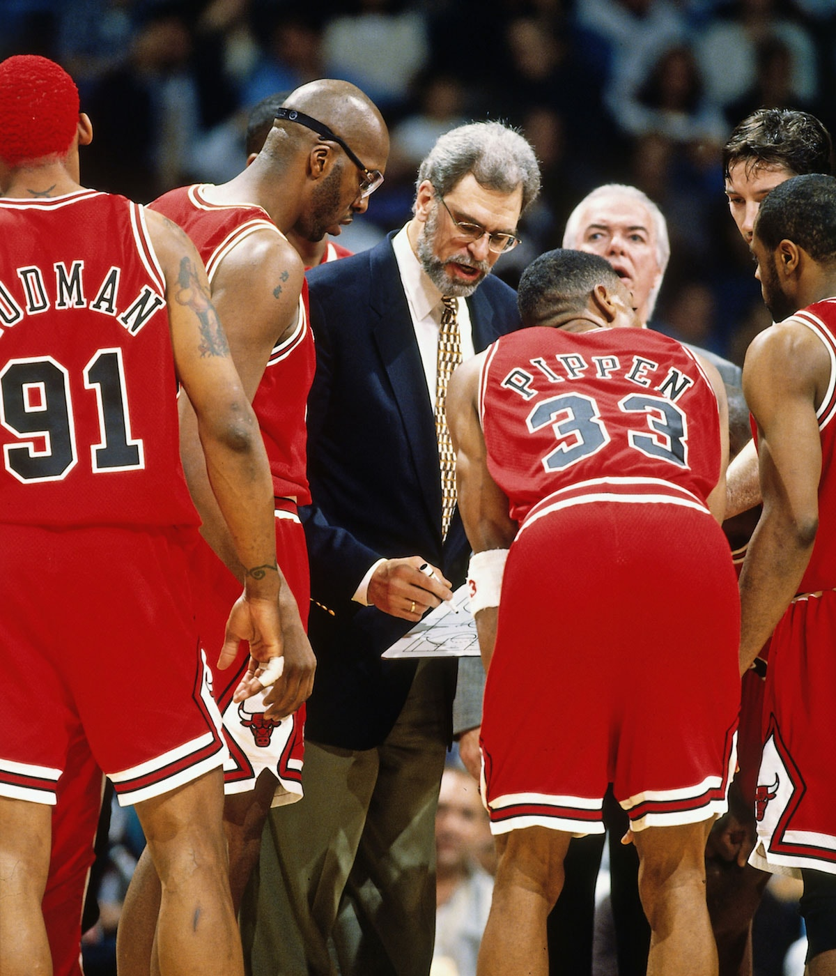 Head Coach Phil Jackson of the Chicago Bulls huddles his team against the Miami Heat on April 2, 1996 at Miami Arena in Miami, Florida.