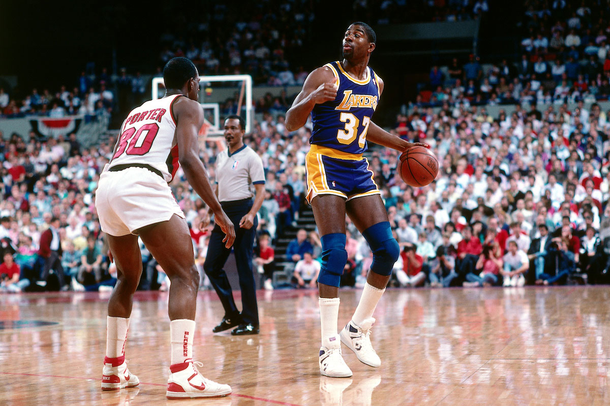 Magic Johnson #32 of the Los Angeles Lakers dribbles the ball against the Portland Trail Blazers during a game played circa 1987 at the Veterans Memorial Coliseum in Portland, Oregon.