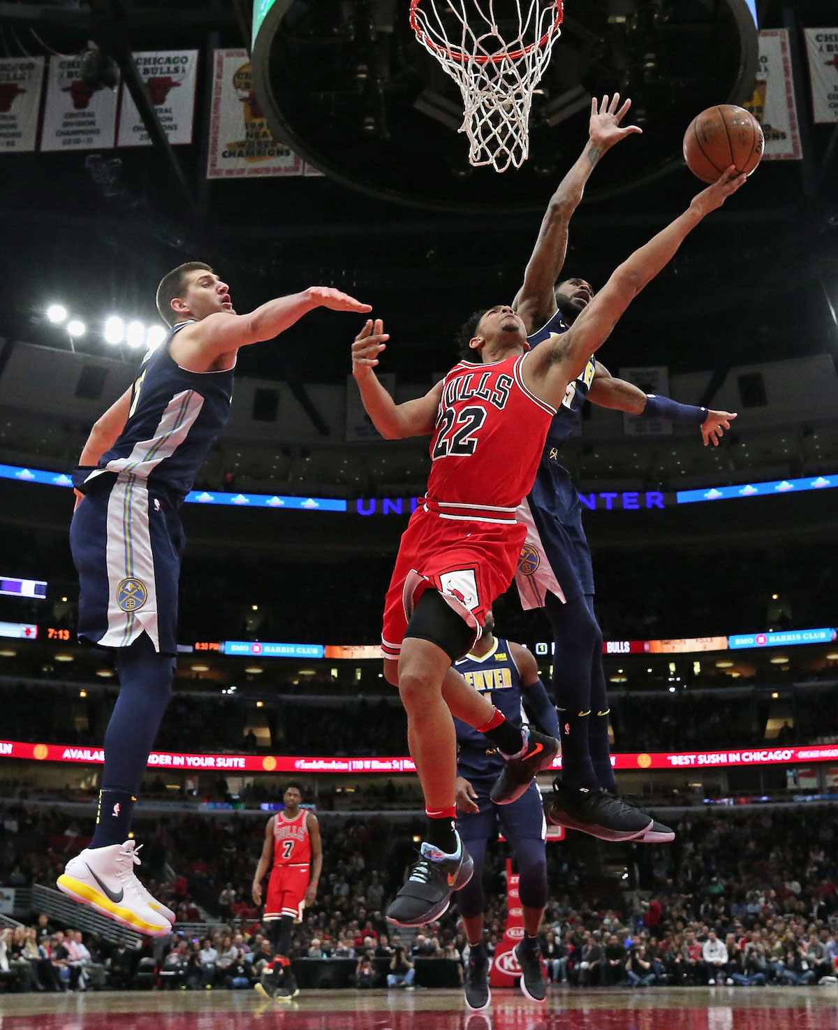 Cameron Payne #22 of the Chicago Bulls goes up for a shot between Nikola Jokic #15 (L) and Will Barton #5 of the Denver Nuggets at the United Center on March 21, 2018 in Chicago, Illinois.