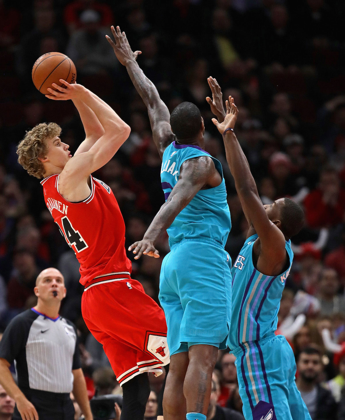 Lauri Markkanen #24 of the Chicago Bulls shoots over Michael Kidd-Gilchrist #14 (R) and Marvin Williams #2 of the Charlotte Hornets at the United Center on April 3, 2018