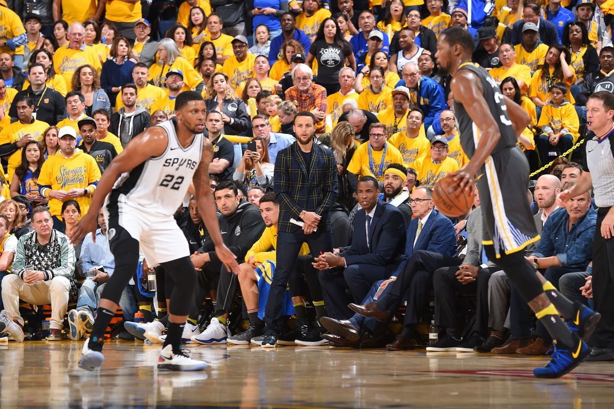 Stephen Curry #30 of the Golden State Warriors watches from the bench against the San Antonio Spurs in Game Two of Round One of the 2018 NBA Playoffs on April 16, 2018 at ORACLE Arena in Oakland, California