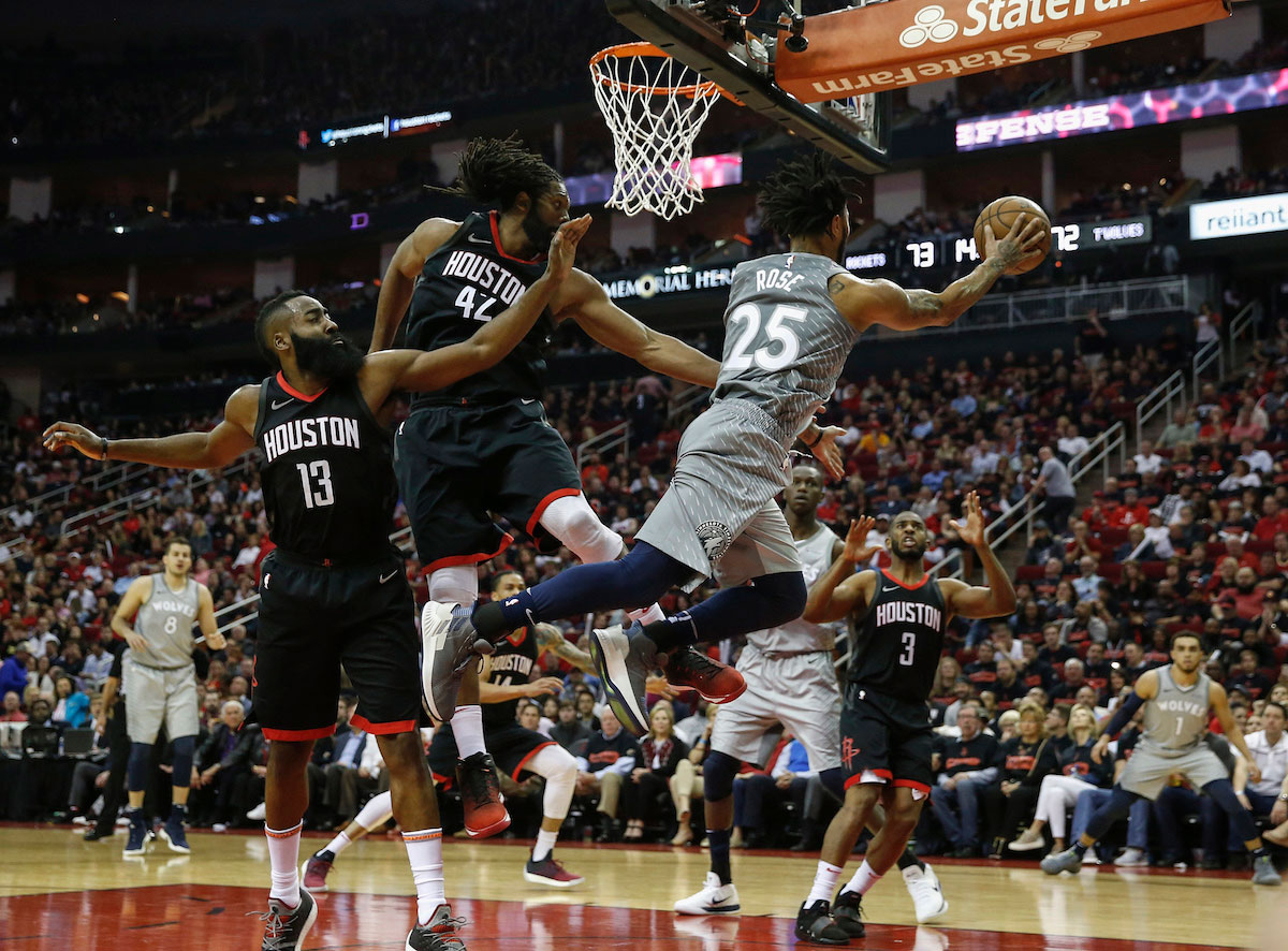 Derrick Rose #25 of the Minnesota Timberwolves passes the ball under the basket against Nene Hilario #42 of the Houston Rockets and James Harden #13 in the second half during Game One of the first round of the 2018 NBA Playoffs at Toyota Center