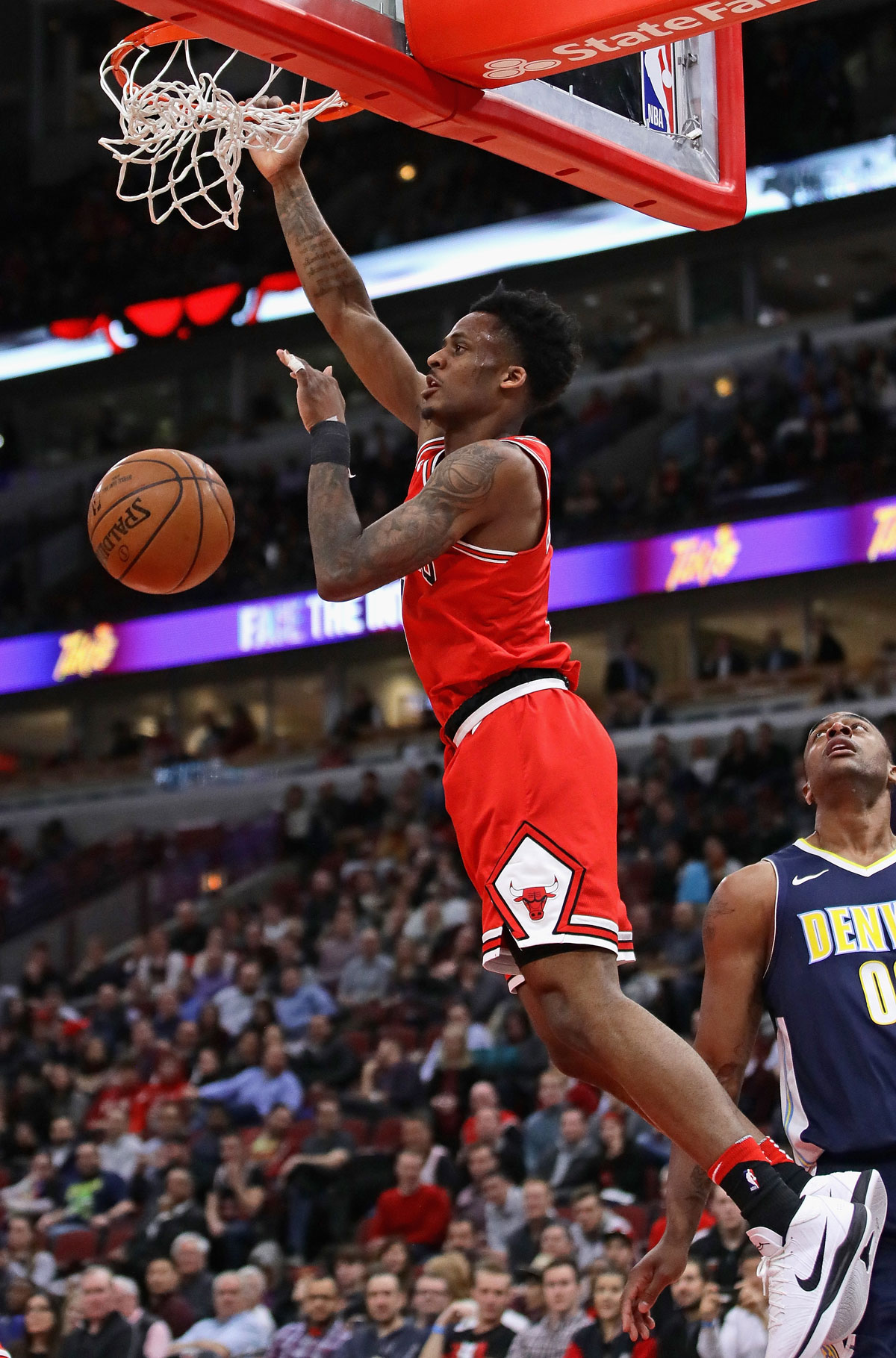 Antonio Blakeney #9 of the Chicago Bulls dunks over Darrell Arthur #00 of the Denver Nuggets at the United Center on March 21, 2018 in Chicago, Illinois.