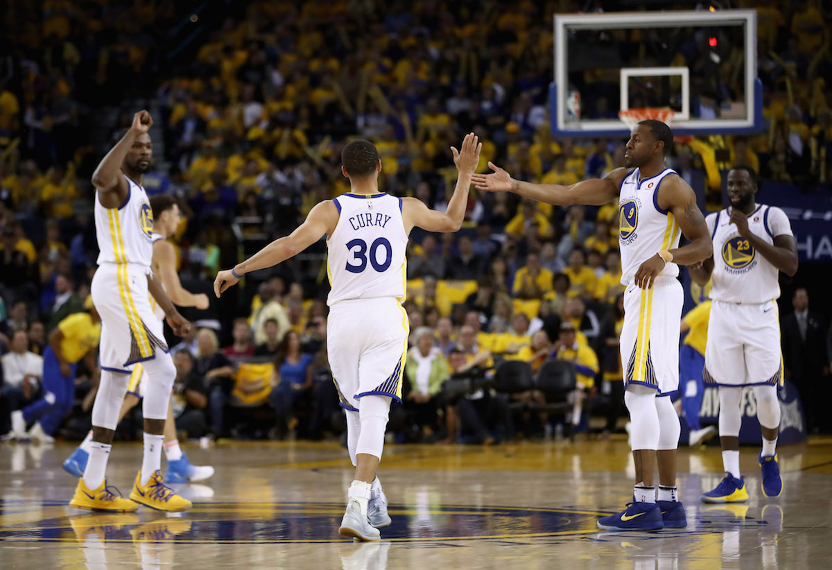 Stephen Curry #30 of the Golden State Warriors is congratulated by Andre Iguodala #9 and Kevin Durant #35 after he made a basket against the New Orleans Pelicans during Game Five of the Western Conference Semifinals of the 2018 NBA Playoffs at ORACLE Arena on May 8, 2018 in Oakland, California.
