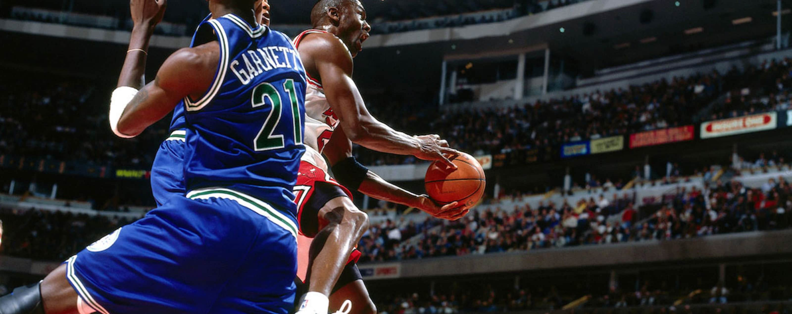 Michael Jordan goes to the hoop defended by Kevin Garnett