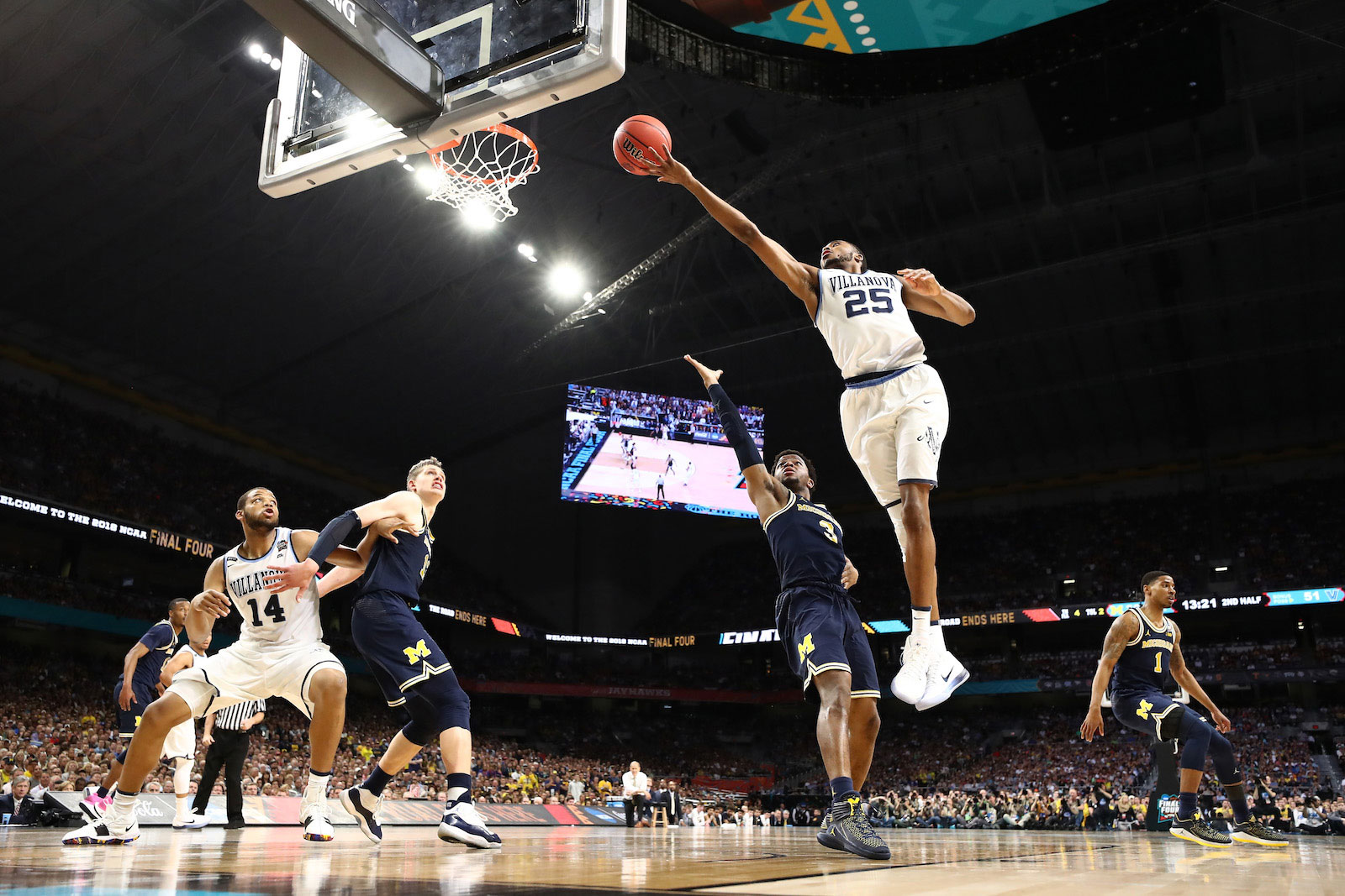 Mikal Bridges #25 of the Villanova Wildcats drives to the basket against Zavier Simpson #3 of the Michigan Wolverines in the second half during the 2018 NCAA Men's Final Four National Championship game at the Alamodome on April 2, 2018 in San Antonio, Texas.