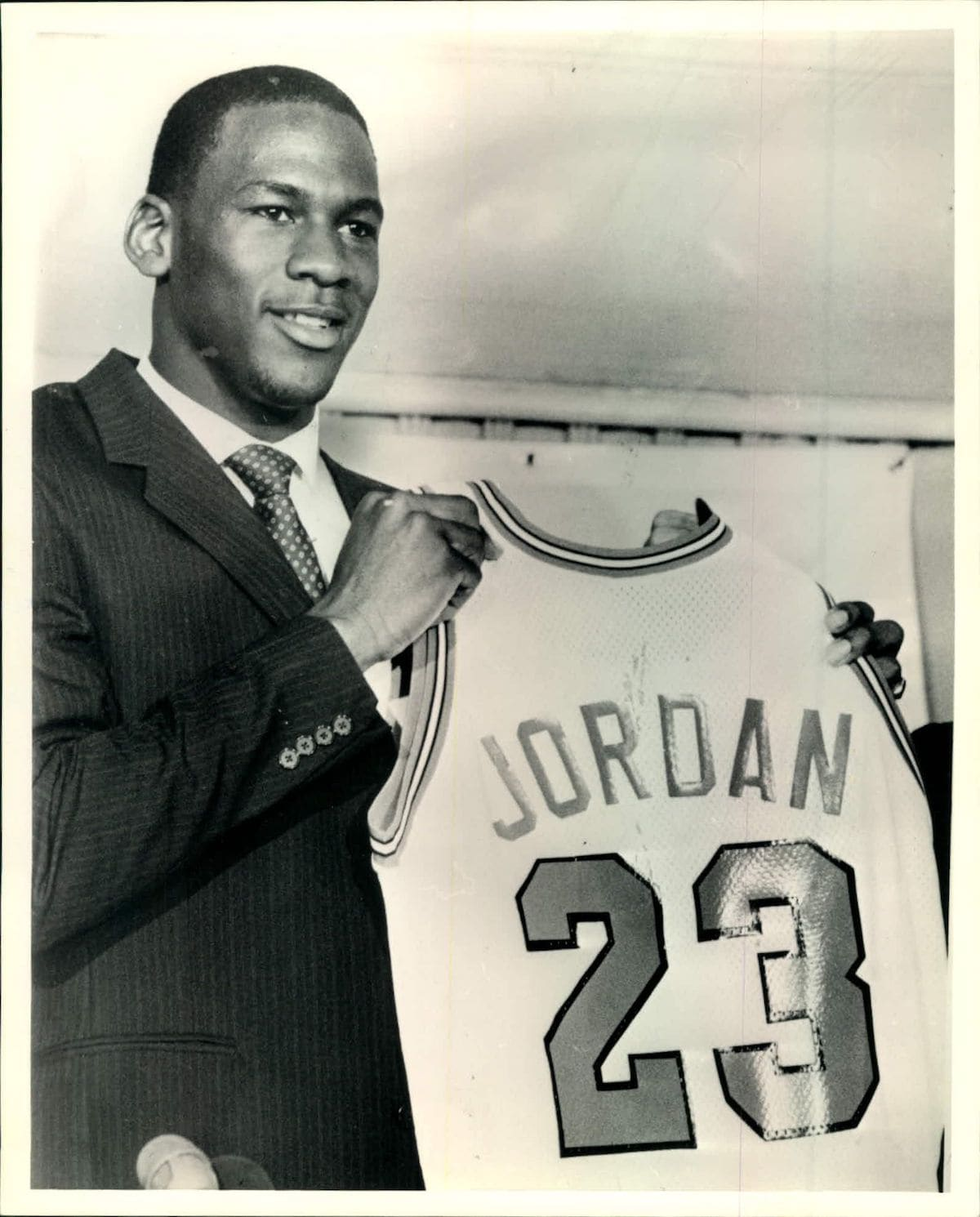 Michael Jordan holds up a Chicago Bulls jersey