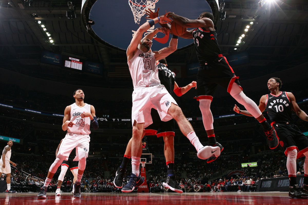 Serge Ibaka #9 of the Toronto Raptors and Marcin Gortat #13 of the Washington Wizards jump for the rebound in Game Four of Round One of the 2018 NBA Playoffs on April 22, 2018 at Capital One Arena in Washington, DC.