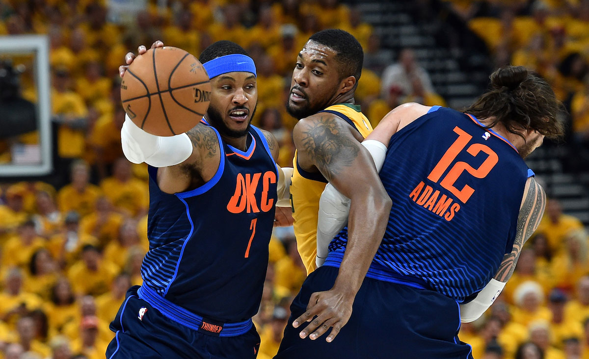Carmelo Anthony #7 of the Oklahoma City Thunder drives past Derrick Favors #15 of the Utah Jazz due to the block by Steven Adams #12 of the Oklahoma City Thunder in the first half during Game Six of Round One of the 2018 NBA Playoffs at Vivint Smart Home Arena on April 27, 2018 in Salt Lake City, Utah.