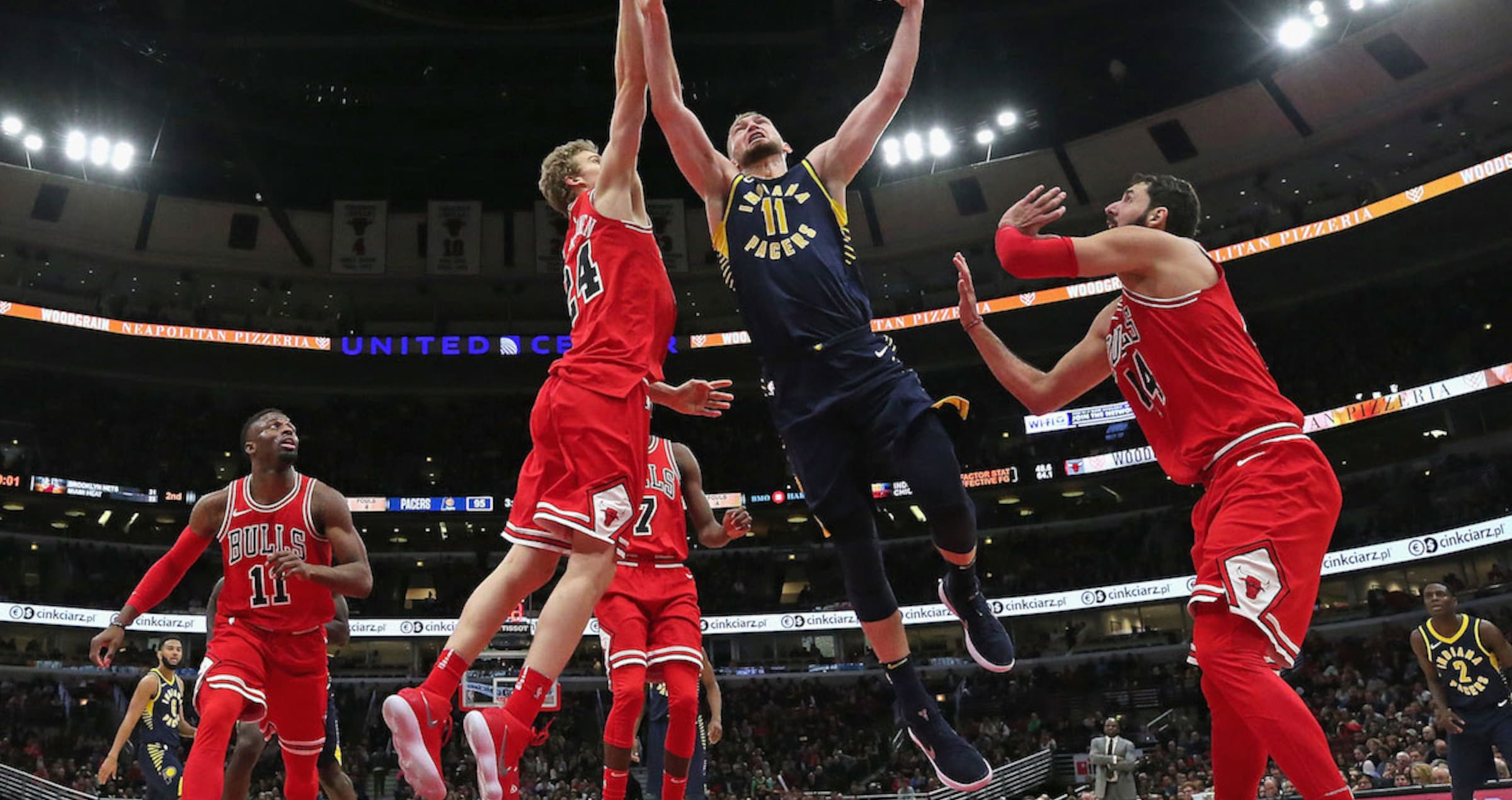 Domantas Sabonis #11 of the Indiana Pacers puts up a shot between Lauri Markkanen #24 and Nikola Mirotic #44 of the Chicago Bulls.