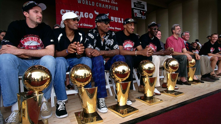 Toni Kukoc, Ron Harper, Dennis Rodman, Scottie Pippen, Michael Jordan, and head coach Phil Jackson sit behind their six championship trophies prior to the Bulls Victory Celebration at Grant Park