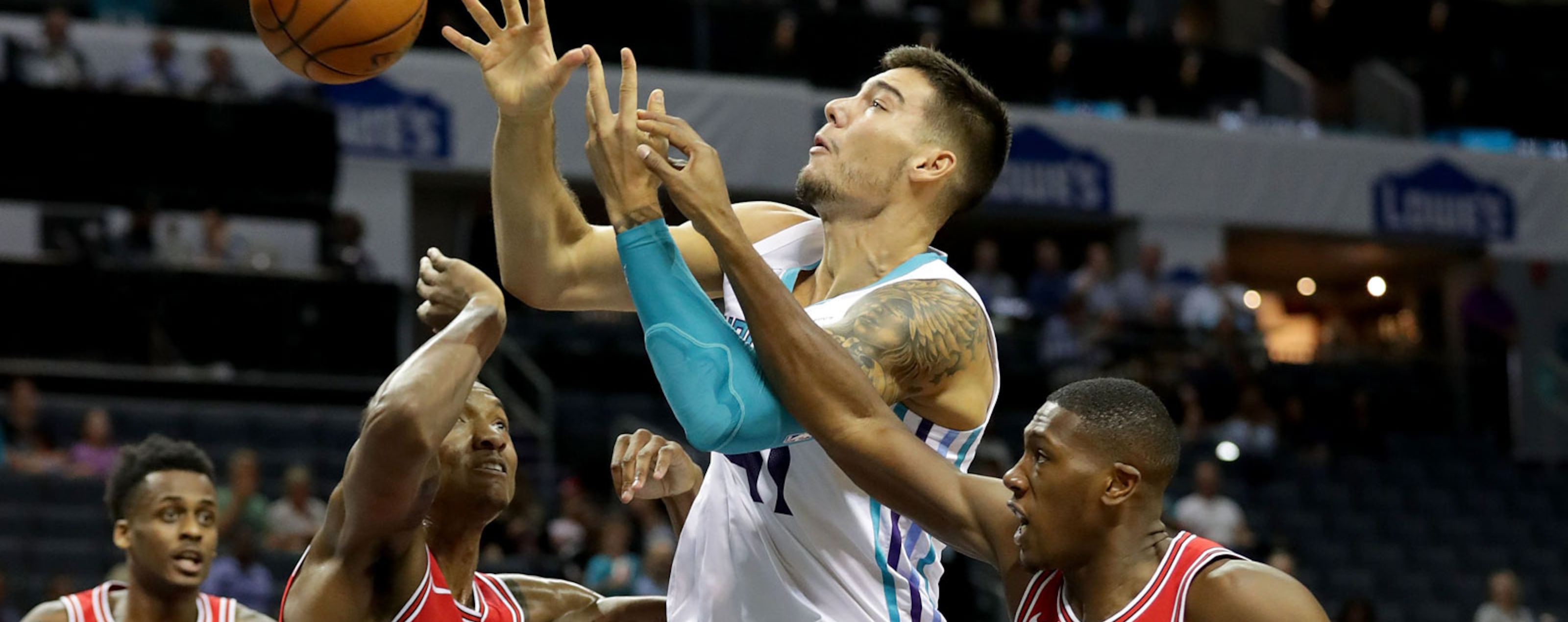 Teammates Wendell Carter Jr. #34 and Kris Dunn #32 of the Chicago Bulls try to stop Willy Hernangomez #41 of the Charlotte Hornets during their game at Spectrum Center on October 8, 2018 in Charlotte, North Carolina.