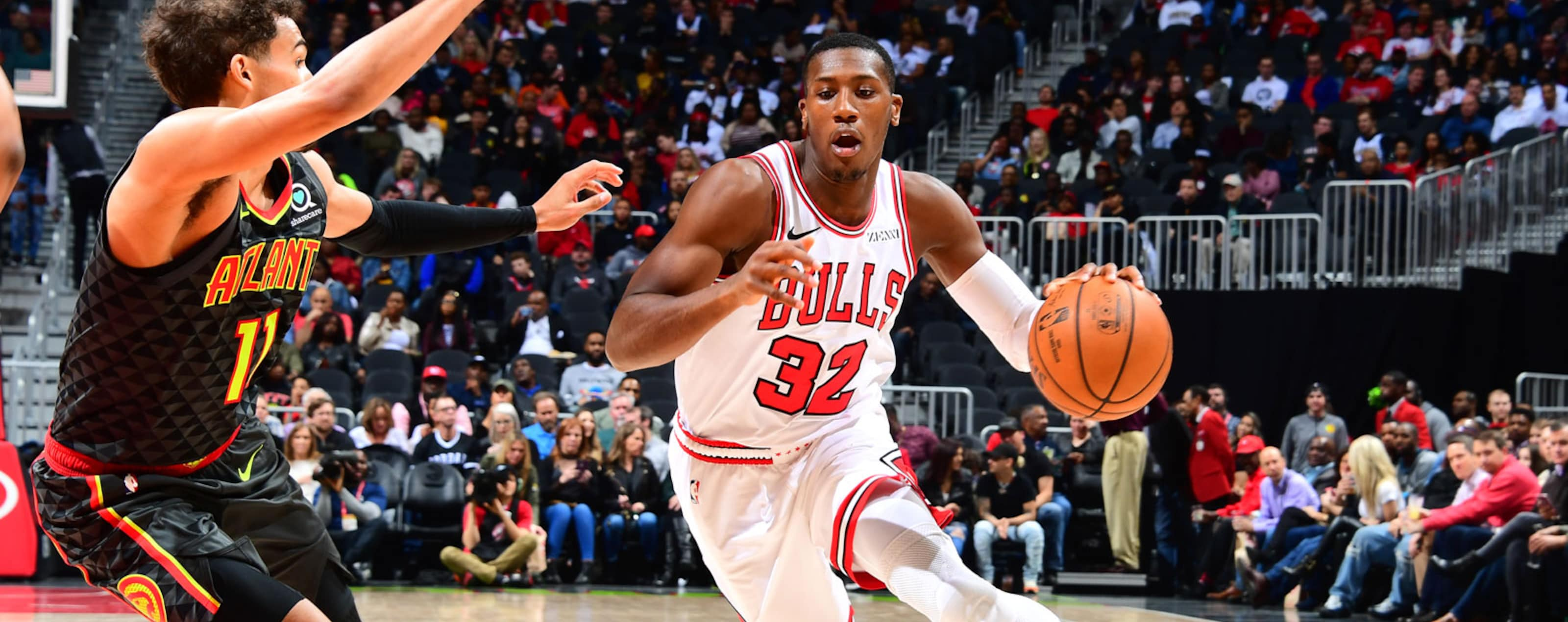 Kris Dunn #32 of the Chicago Bulls drives past Trae Young #11 of the Atlanta Hawks on March 1, 2019 at State Farm Arena in Atlanta, Georgia.