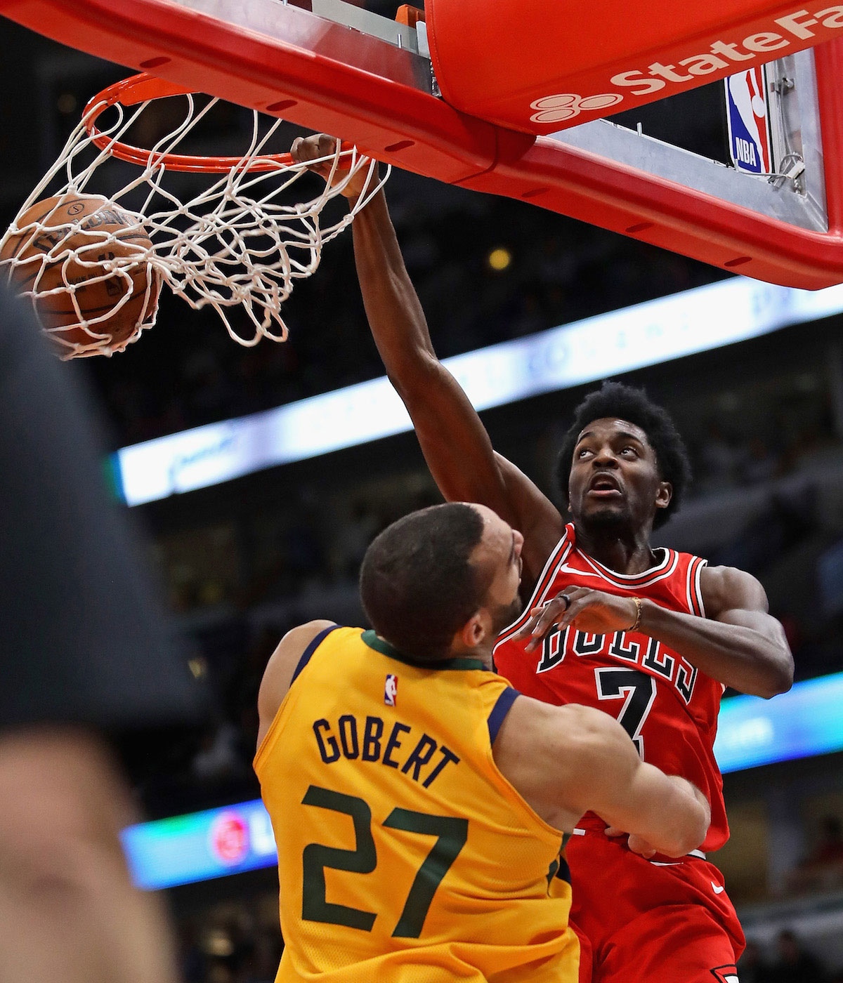Justin Holiday #7 of the Chicago Bulls dunks over Rudy Gobert #27 of the Utah Jazz at the United Center on December 13, 2017 in Chicago, Illinois.