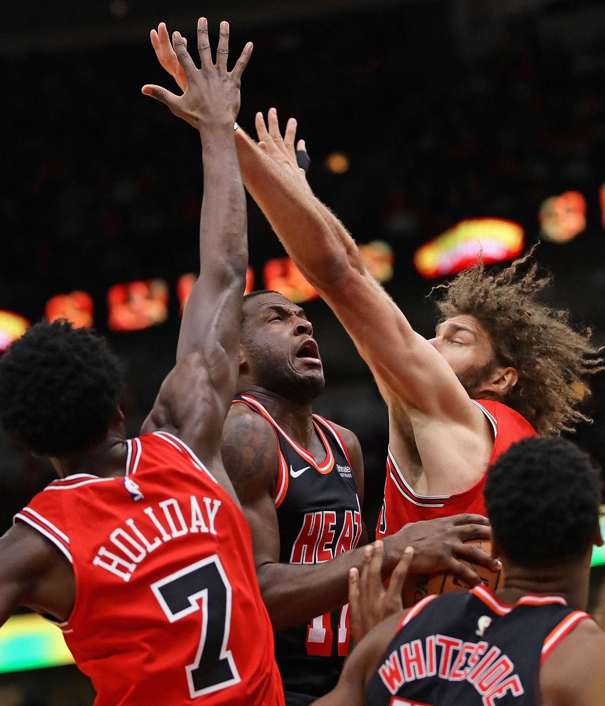 Dion Waiters #11 of the Miami Heat drives between Justin Holiday #7 and Robin Lopez #42 of the Chicago Bulls at the United Center on November 26, 2017 in Chicago, Illinois.