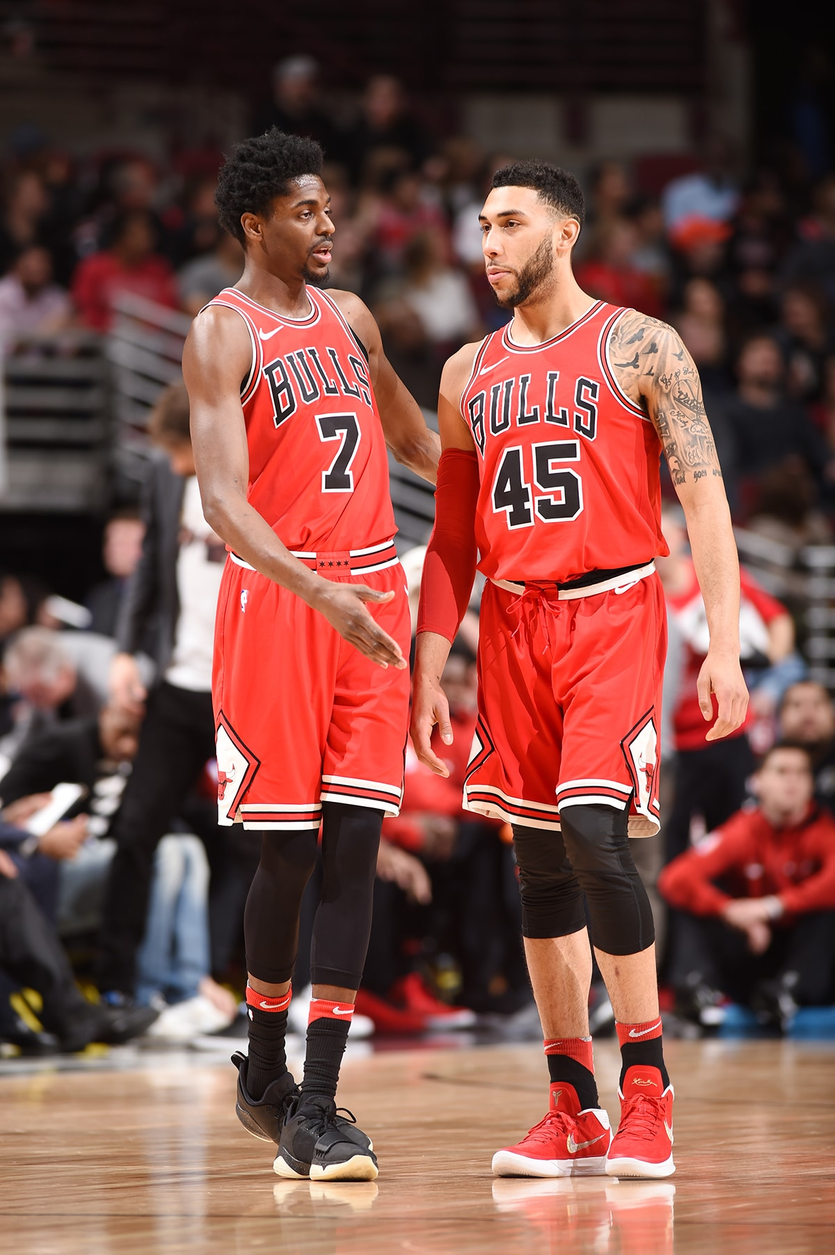 Justin Holiday of the Chicago Bulls talks things over with Denzel Valentine