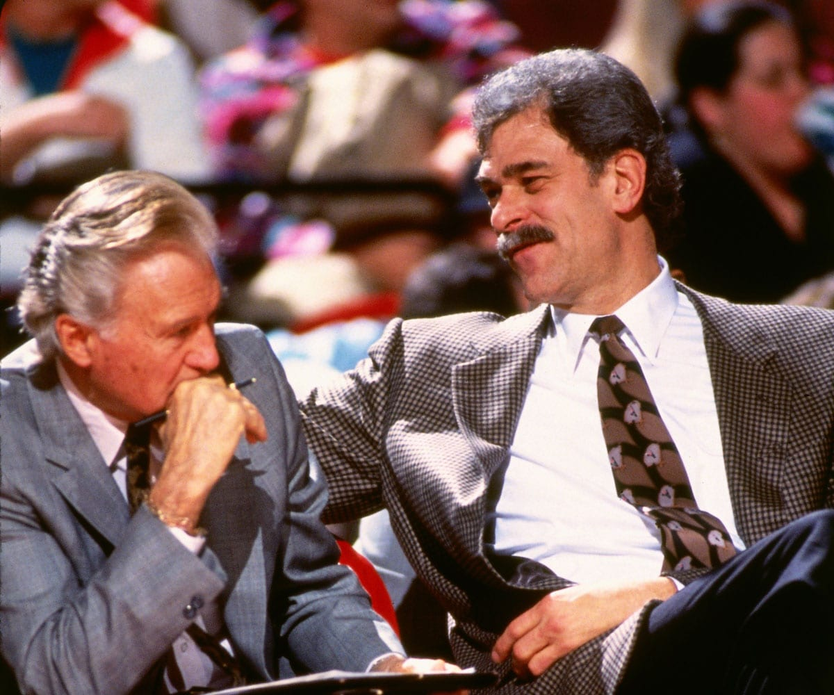 Johnny Bach, assistant coach of the Chicago Bulls talks with head coach Phil Jackson during a game played in 1994 in Chicago, Illinois.