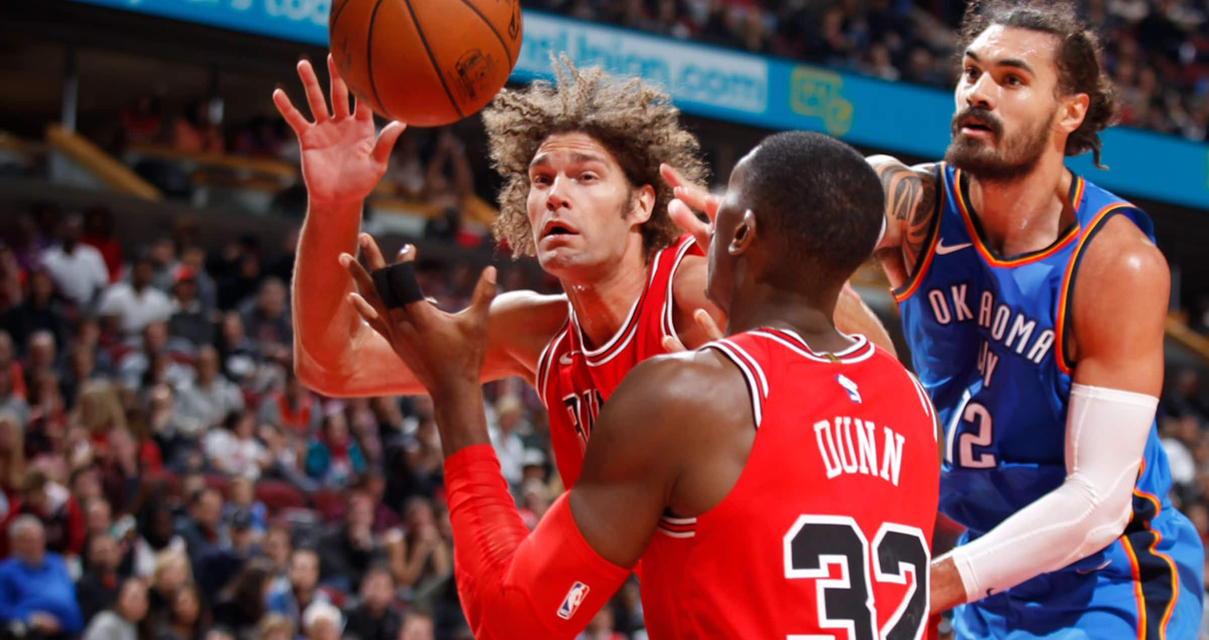 Robin Lopez and Kris Dunn of the Chicago Bulls passing the ball in a game against the Oklahoma City Thunder on October 28, 2017 at the United Center