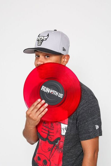 Photo of DJ Metro posing with a red record