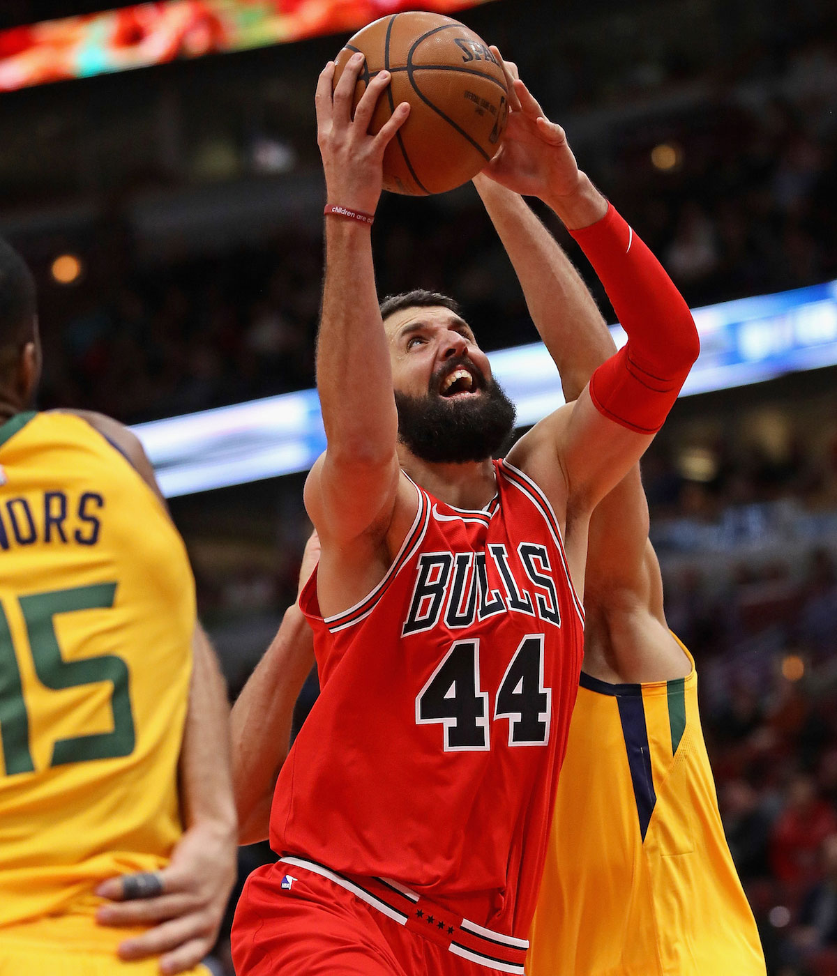 Nikola Mirotic #44 of the Chicago Bulls drives between Derrick Favors #15 (L) and Rudy Gobert #27 of the Utah Jazz at the United Center on December 13, 2017 in Chicago, Illinois.