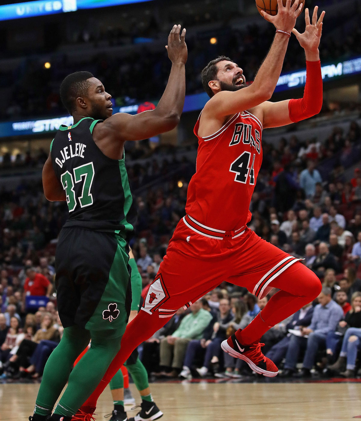 Nikola Mirotic #44 of the Chicago Bulls drives past Semi Ojeleye #37 of the Boston Celtics on his way to a game-high 24 points at the United Center on December 11, 2017 in Chicago, Illinois.