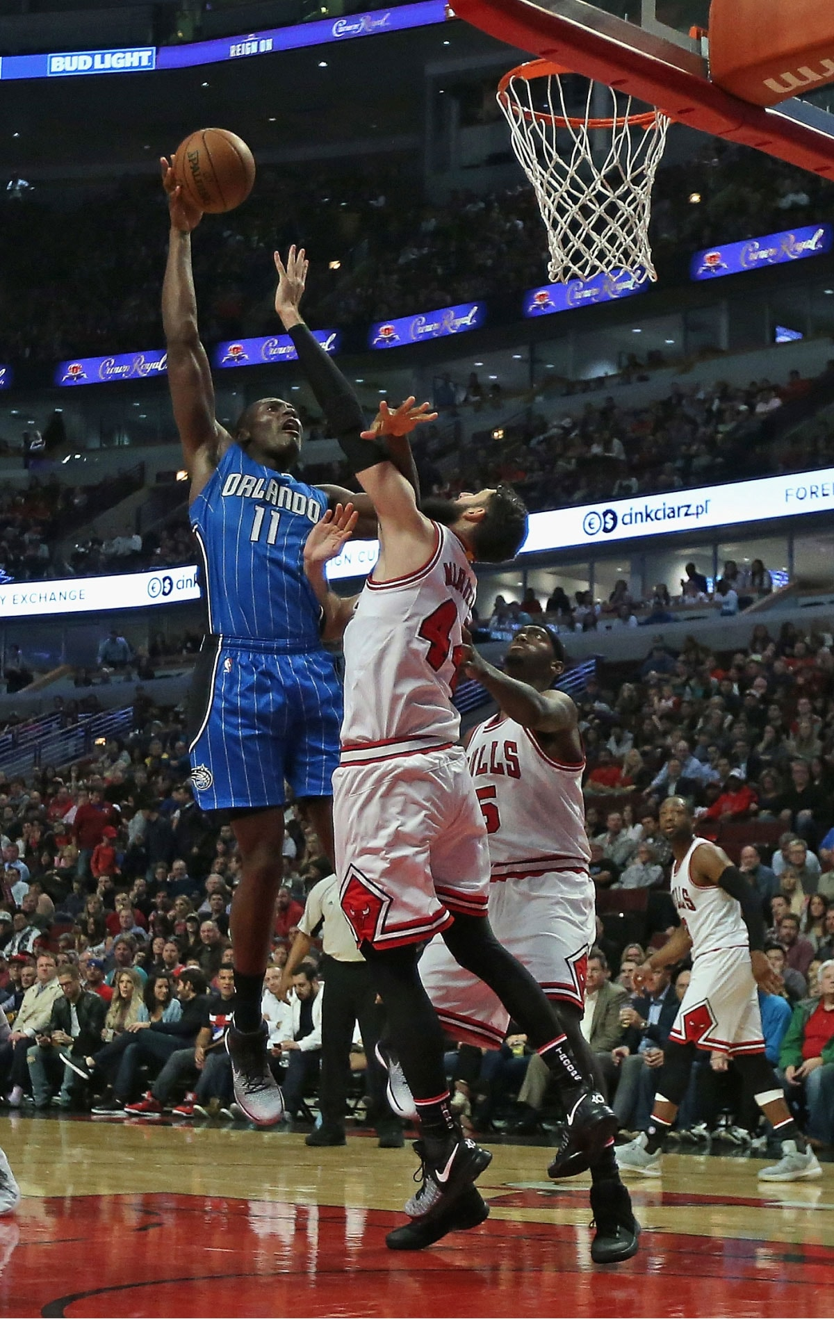Bismack Biyombo #11 of the Orlando Magic shoots over Nikola Mirotic #44 and Bobby Portis #5 of the Chicago Bulls at the United Center on November 7, 2016 in Chicago, Illinois.