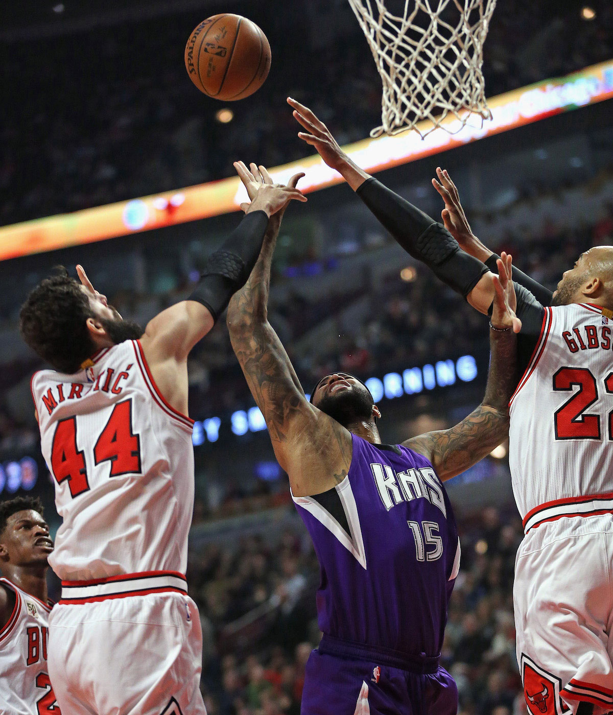 DeMarcus Cousins #15 of the Sacramento Kings Battles for a rebound between Nikola Mirotic #44 and Taj Gibson #22 of the Chicago Bulls at the United Center on March 21, 2016 in Chicago, Illinois.