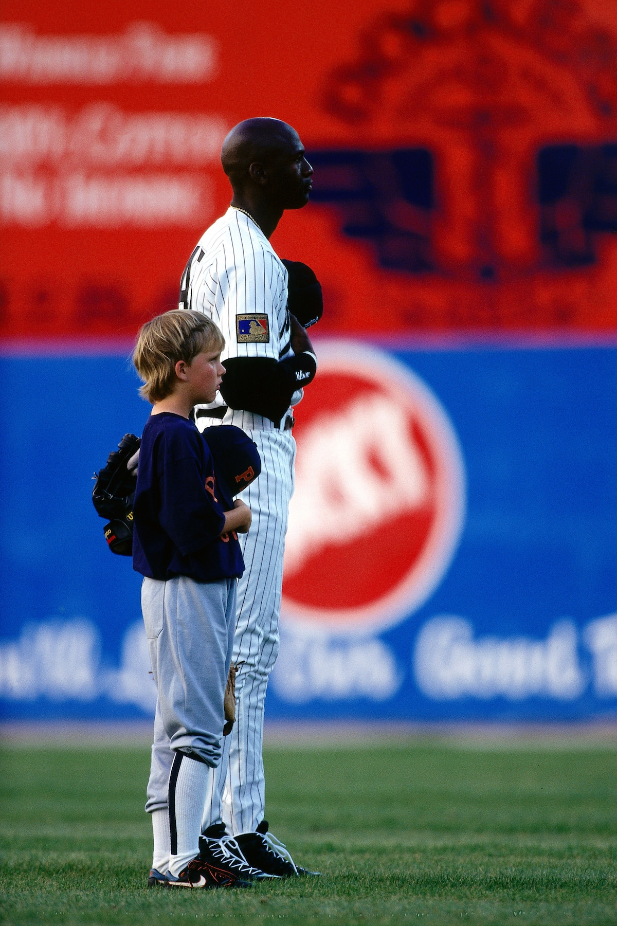 Michael Jordan, in minor league baseball attire, stands next to a child during the National Anthem.