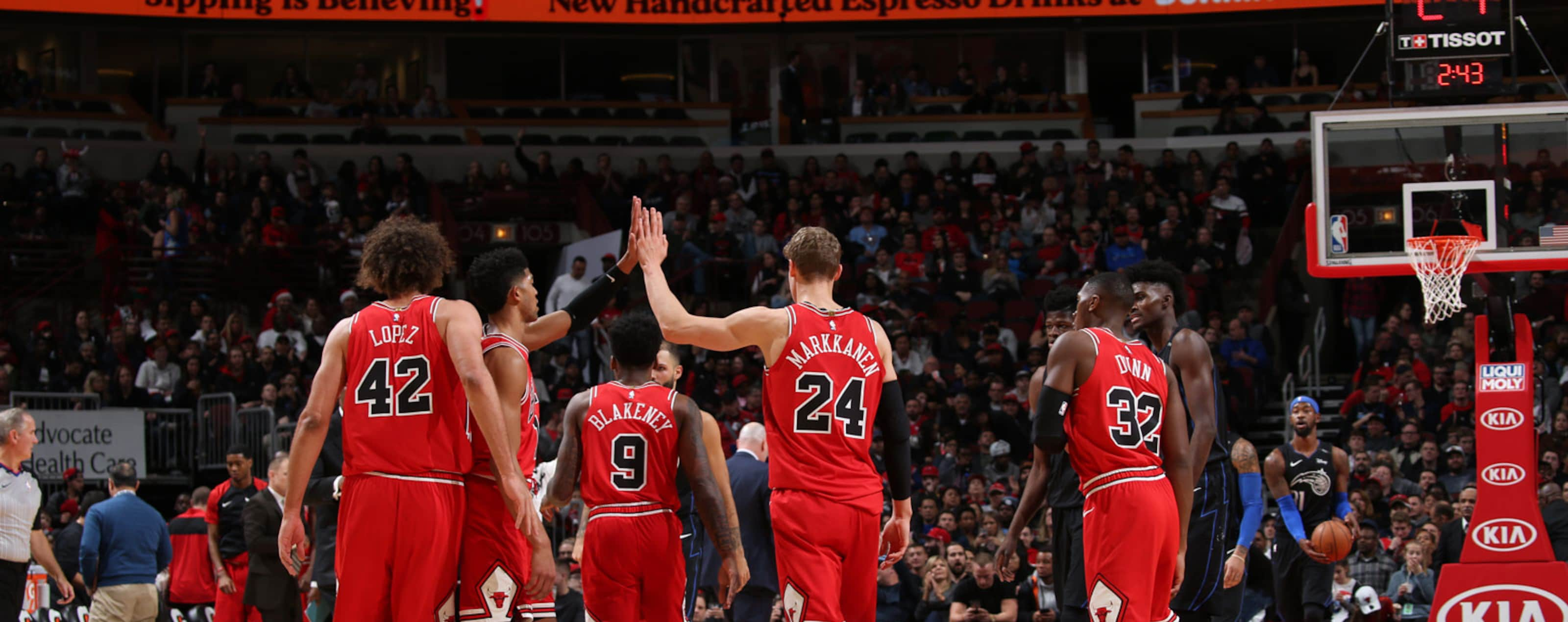 Chicago Bulls players high-five one another while walking to the bench.