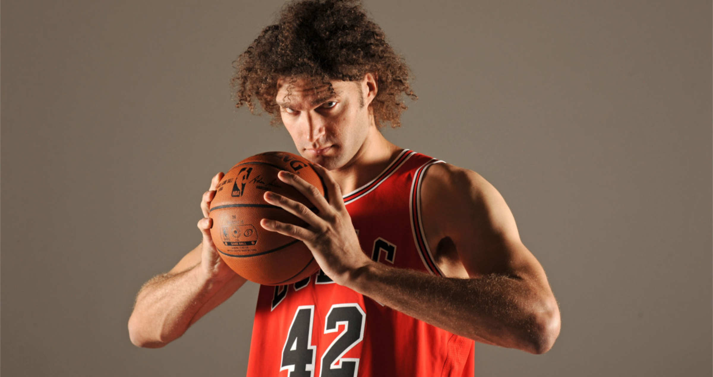 Robin Lopez on Chicago Bull's Media Day posing with a basketball.