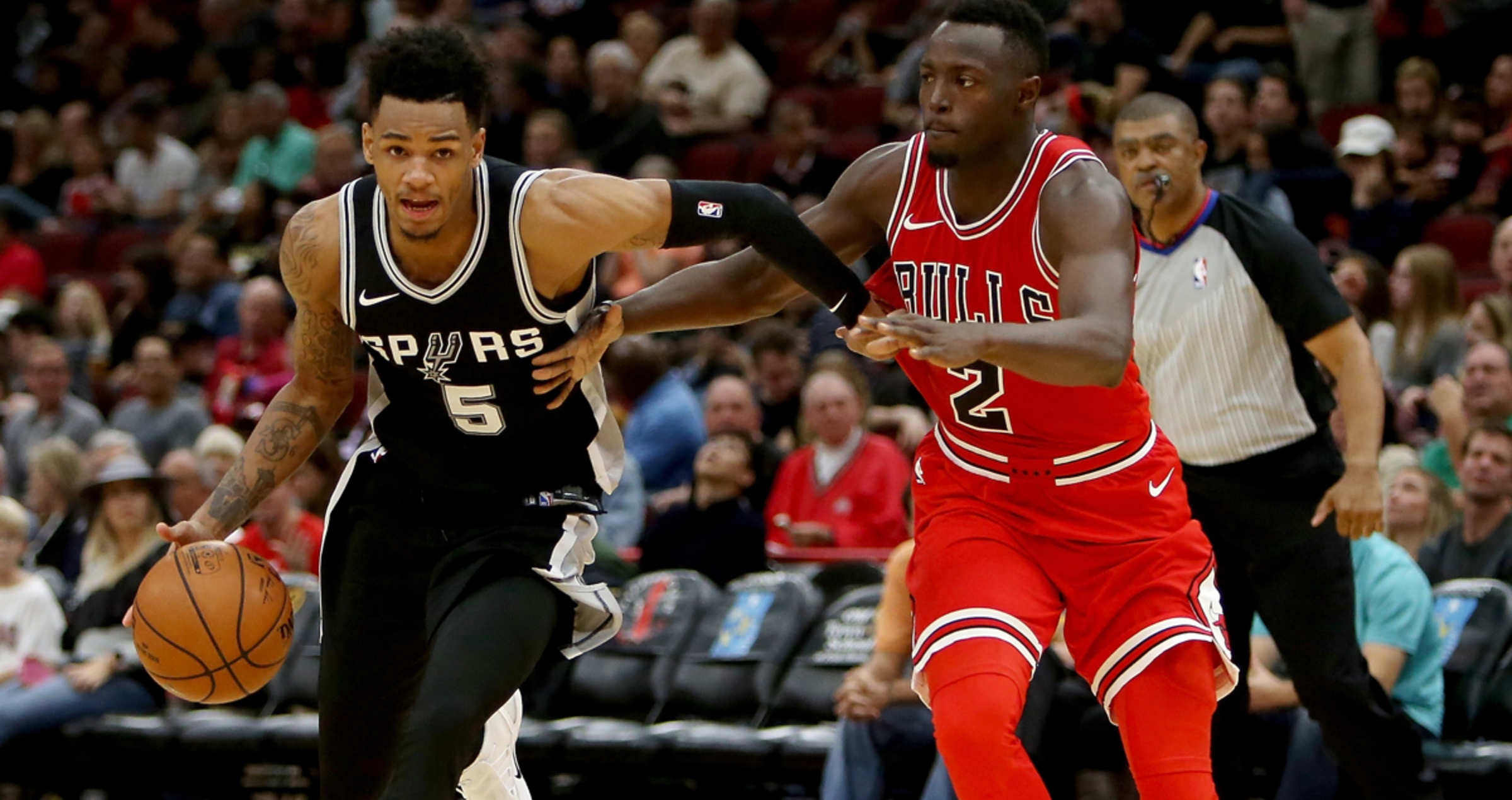 Dejounte Murray #5 of the San Antonio Spurs dribbles the ball while being guarded by Jerian Grant #2 of the Chicago Bulls in the third quarter at the United Center on October 21, 2017 in Chicago, Illinois.
