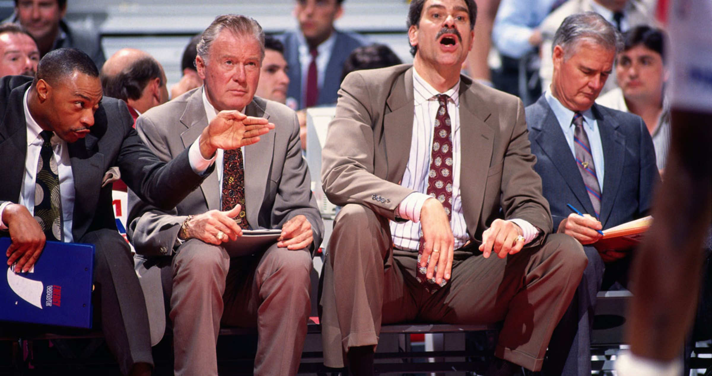 Jim Cleamons, Johnny Bach, head coach Phil Jackson and Tex Winter of the Chicago Bulls sit on the bench during the 1990 season at Chicago Stadium in Chicago, Illinois.