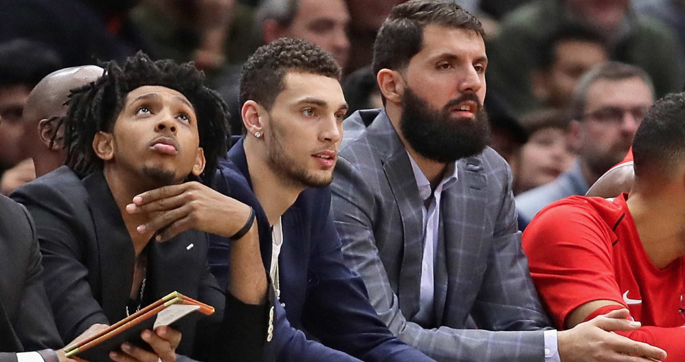 Injured Chicago Bulls players Cameron Payne, Zach LaVine and Nikola Mirotic sit on the bench during a game against the Phoenix Suns at the United Center on November 28, 2017 in Chicago, Illinois.