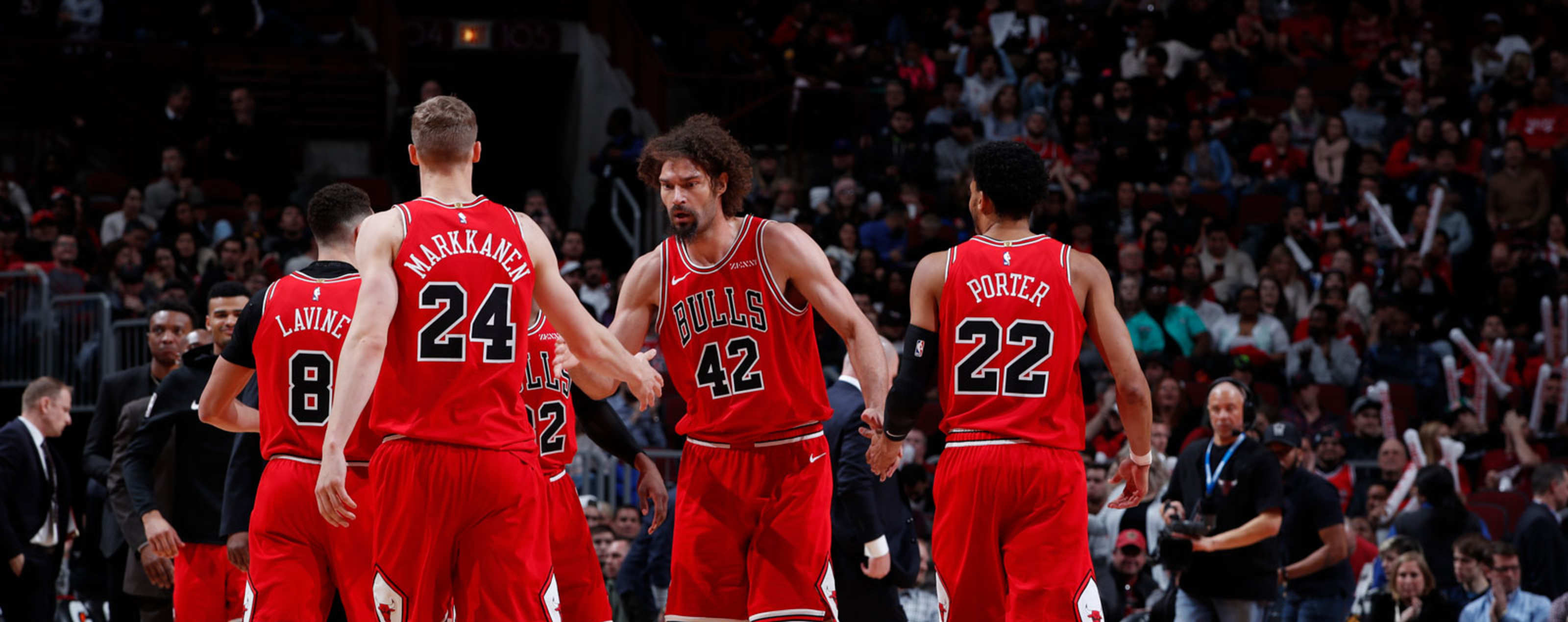 Lauri Markkanen high fives Robin Lopez during a game at the United Center.