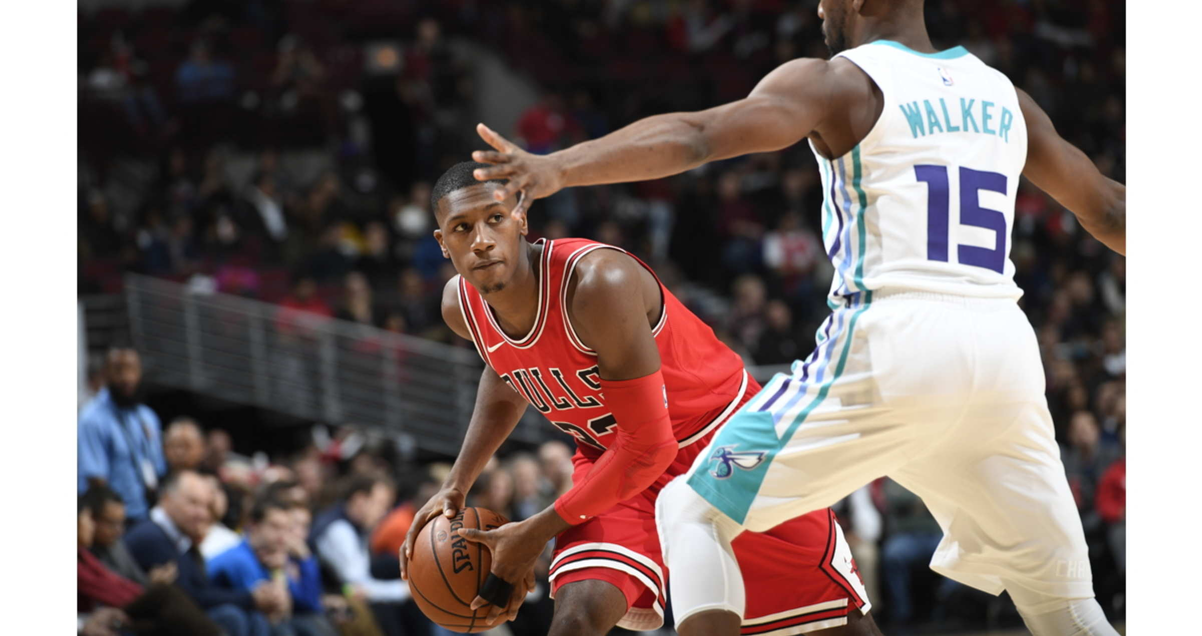 Kris Dunn looks to pass around Kemba Walker