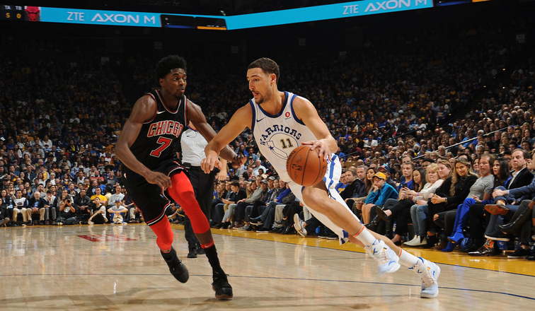 Klay Thompson of the Golden State Warriors driving against Justin Holiday of the Chicago Bulls