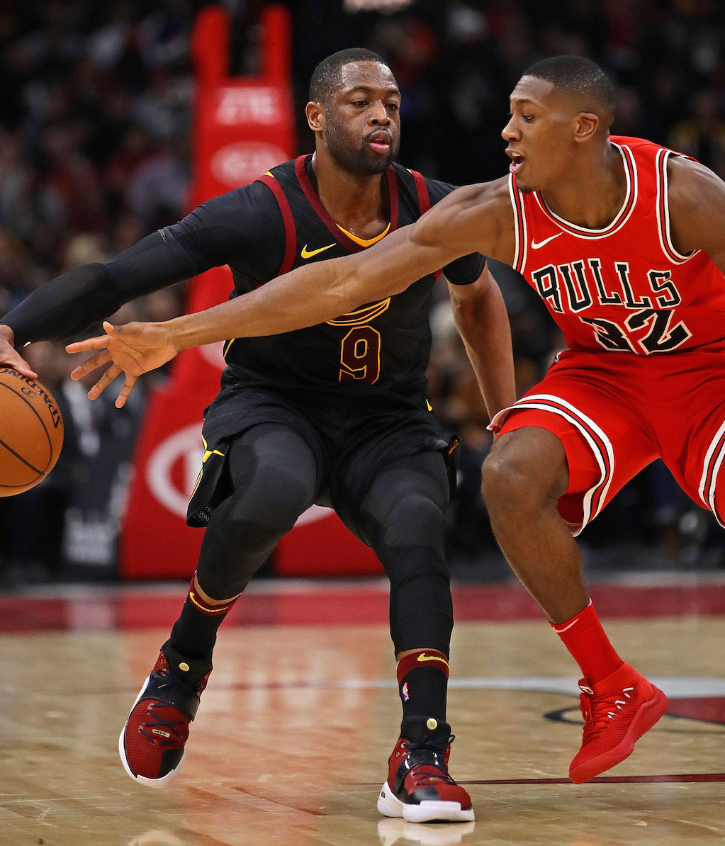 Kris Dunn #32 of the Chicago Bulls tries to knock the ball away from Dwyane Wade #9 of the Cleveland Cavaliers at the United Center on December 4, 2017 in Chicago, Illinois.