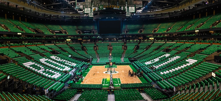 "A wide shot of the interior of TD Garden, with every seat covered in a green T-shirt, and with ""BOS"" and ""617"" spelled out in white T-shirts"