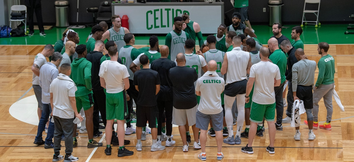 The Celtics surround Brad Stevens at the center of the Auerbach Center during Day 2 of training camp