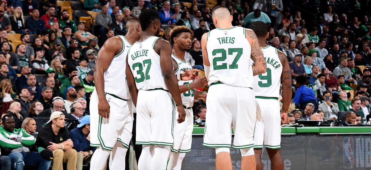 Marcus Smart stands in the center of a Celtics huddle