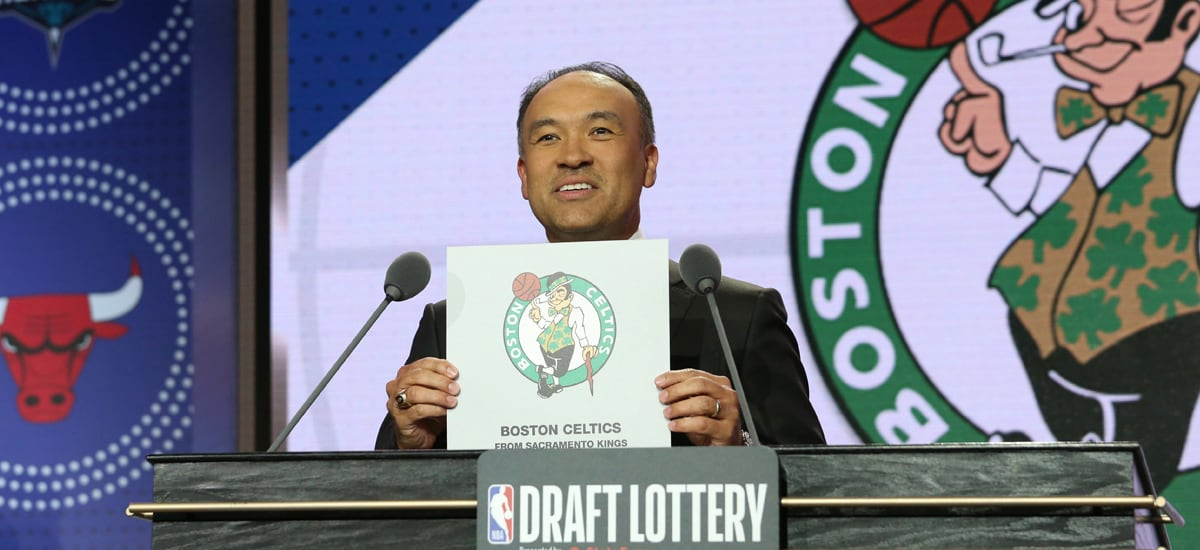 The Deputy Commissioner holds up Boston's logo at the 2019 NBA Draft Lottery.