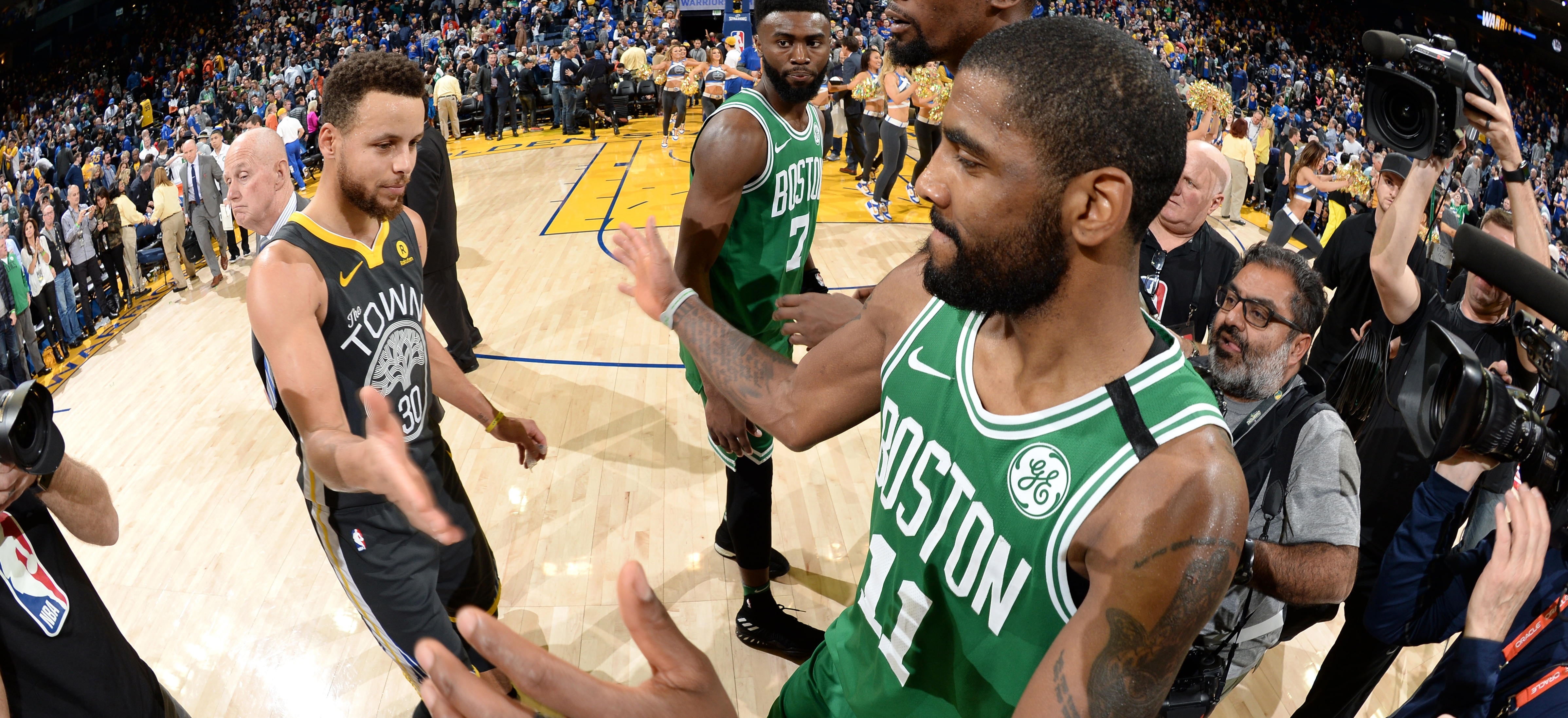 Stephen Curry and Kyrie Irving slap hands after the Warriors fend off the Celtics in Oakland