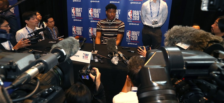 Rui Hachimura sits at a table in front of a large crowd of Japanese reporters