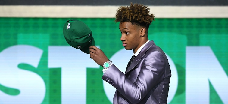 Romeo Langford tips his Celtics hat on stage at the NBA Draft