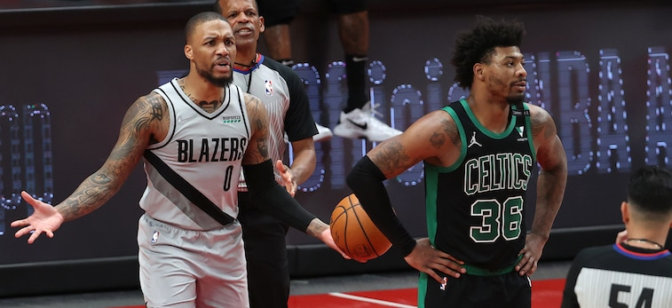 Damian Lillard stands behind Marcus Smart with his hands wide and raised to his sides