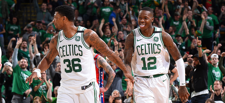 Marcus Smart and Terry Rozier celebrate while walking next to each other on the parquet