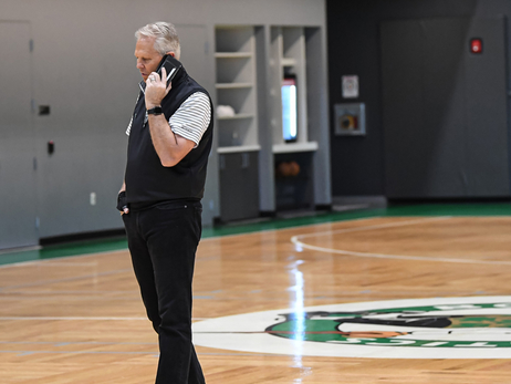 Danny Ainge talks on his cell phone while walking on the court at the Auerbach Center