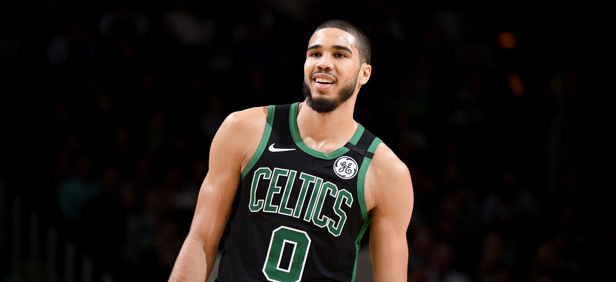 Jayson Tatum smiles while leaning to his left